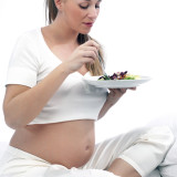 Pregnant woman in bed eating salad